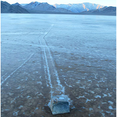 GPS-instrumented rock with its rock trail.The GPS unit with its battery pack is inserted into a cavity bored into the top of the rock. The GPS continuously logs its position after a switch is triggered by the stone moving away from a magnet set in the playa. The surface of the playa is frozen in this image, but the ice had melted or was floating when the trail formed. Image by Mike Hartmann.